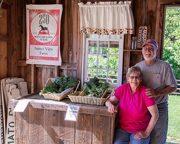 Sunset View Farm owners Chuck and Livvy Tarleton at their farm stand in Winchendon
